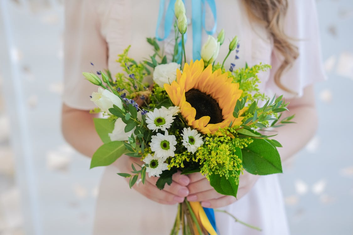 Crop anonymous female with long wavy blond hair in elegant dress holding bunch of delicate fresh wildflowers in light room