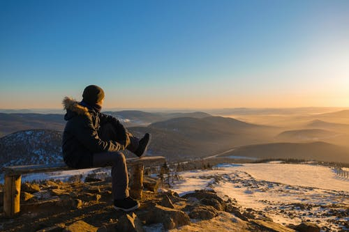 Anonymous traveler resting on bench on mountain top under cloudless sundown sky