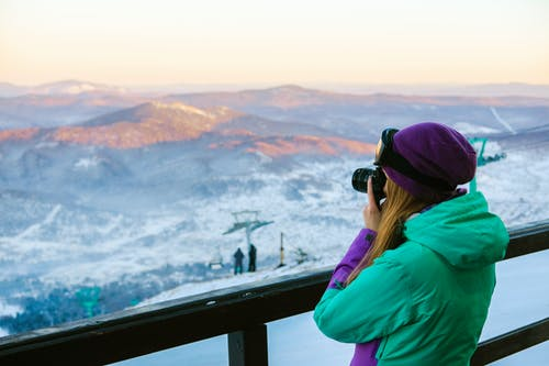 Woman in Green Hoodie Taking Photo of Mountains
