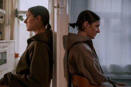 Woman in Brown Coat Standing Beside White Wooden Door