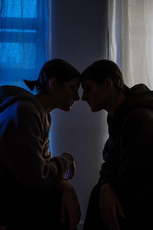 Man in White Long Sleeve Shirt Kissing Woman in Blue Hoodie