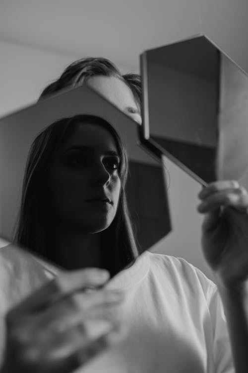 Woman in White Shirt Holding Mirror