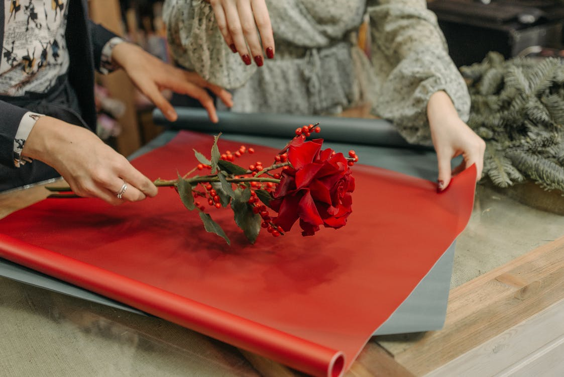 Two Women Wrapping A Red Rose With Color Paper