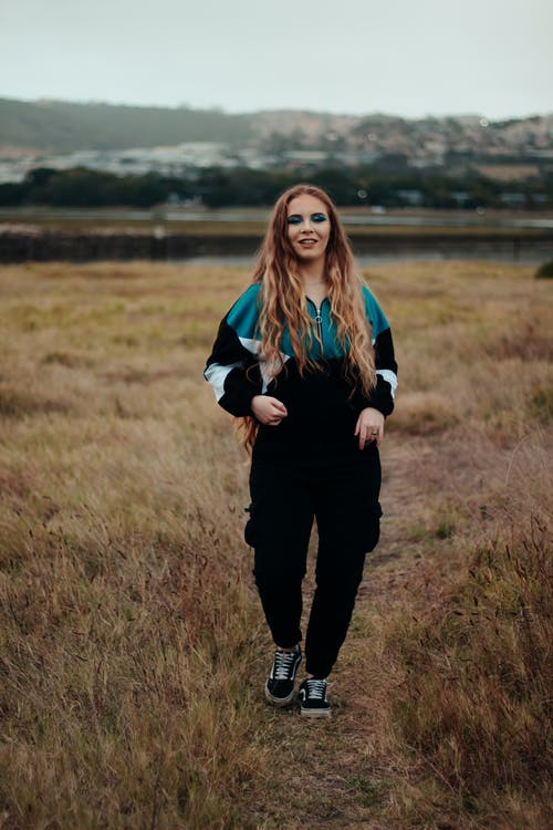 Woman walking on path in grassy countryside field