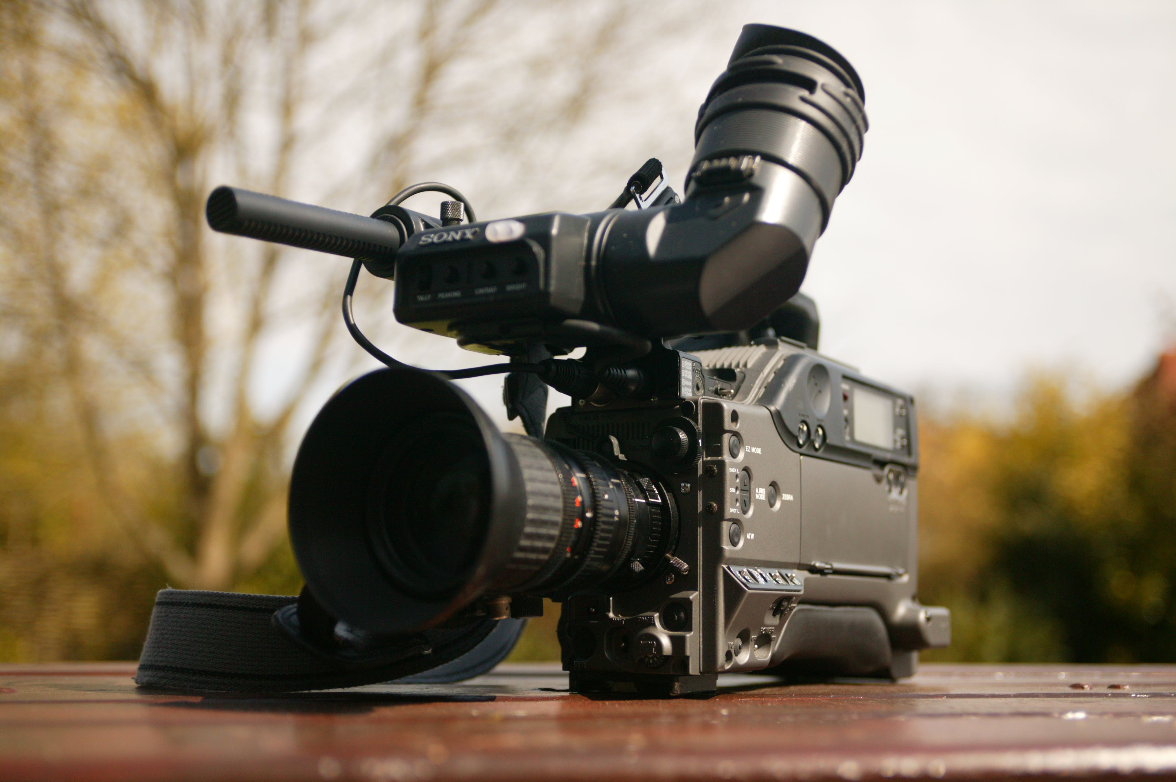 Black Video Camera on Brown Wooden Table