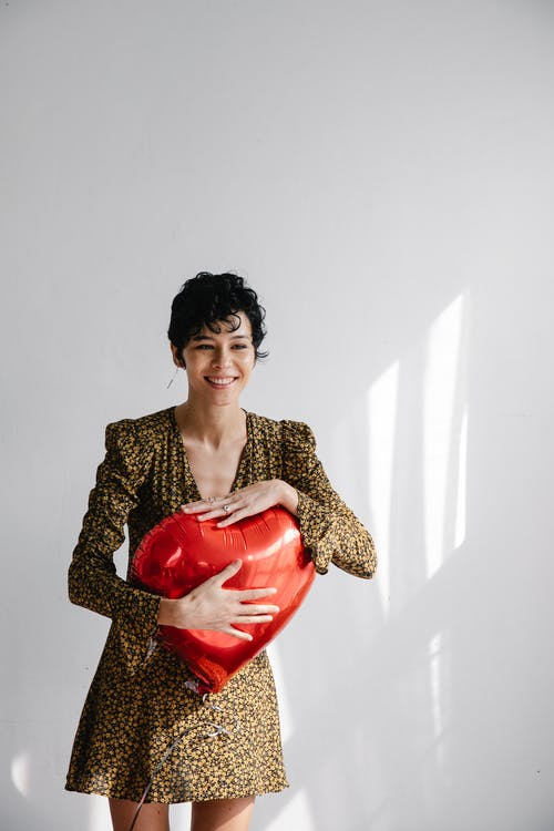 Young stylish woman in trendy dress with heart shaped balloon