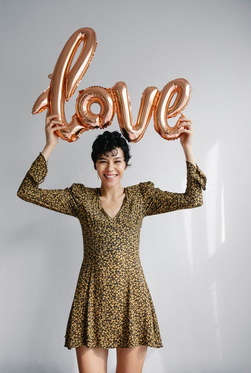 Stylish young female with dark short hair in trendy dress demonstrating pink balloon with word love