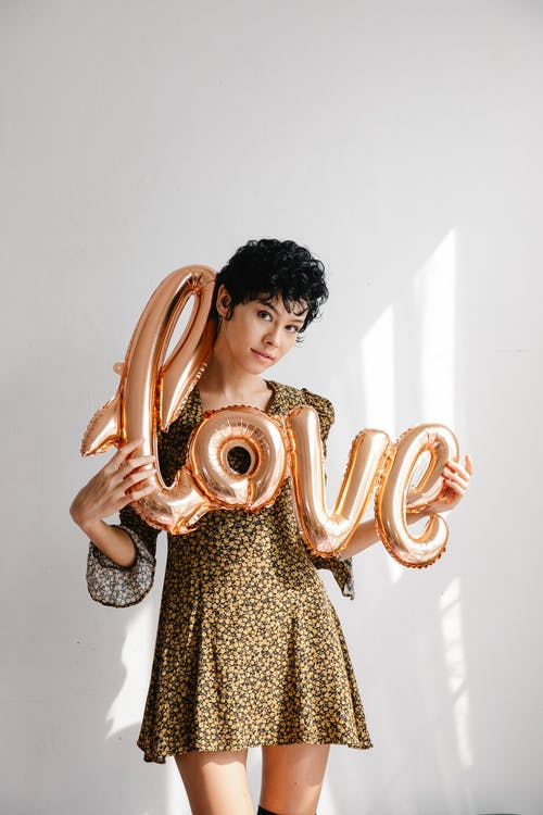 Trendy young woman showing sparkling pink balloon with word love