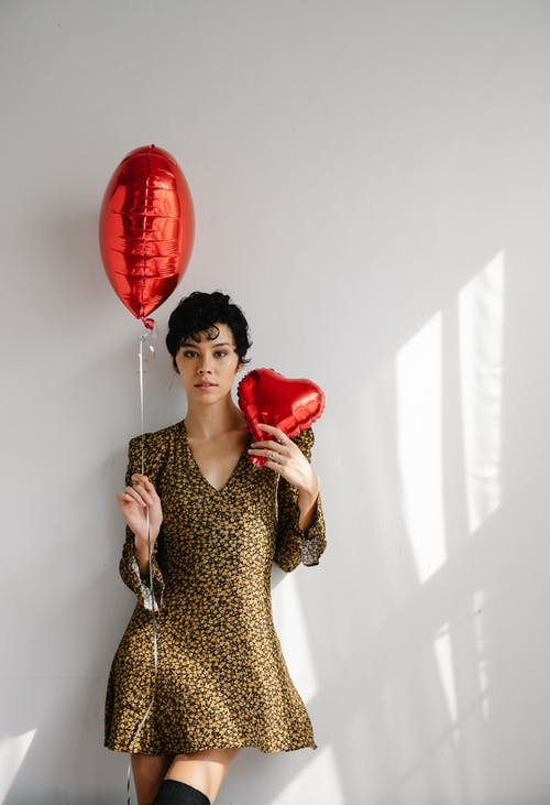 Young slender woman in trendy dress with red balloons