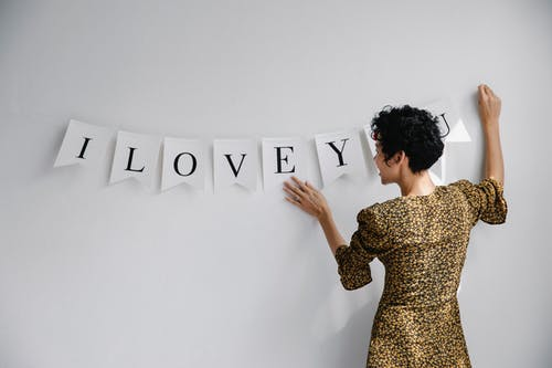 Back view of smiling female decorating white wall with inscription a love you for surprise