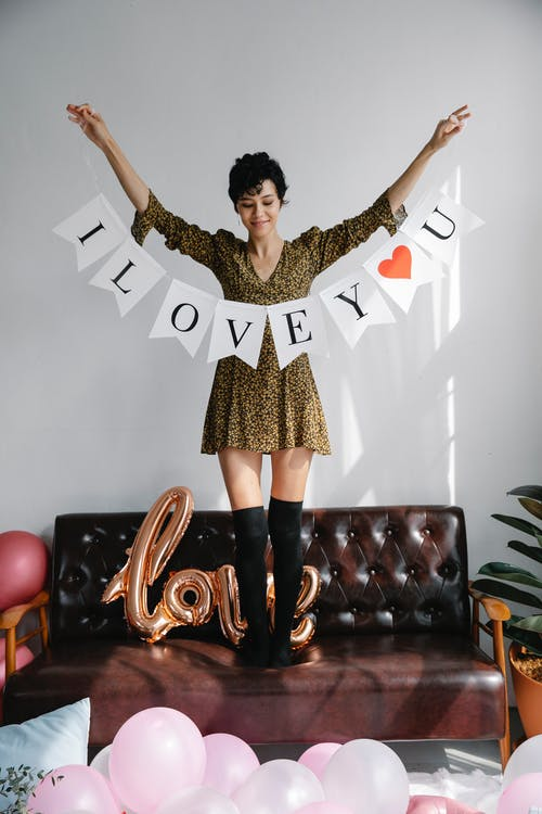 Full body of smiling female standing on couch with flag garland with i love you words for surprise