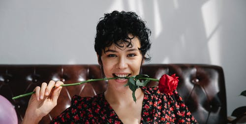 Positive female with curly hair smiling widely while sitting near sofa with blooming rose in mouth and looking at camera