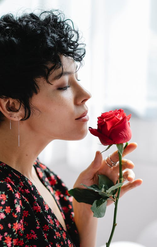 Woman smelling red rose flower with thin petals