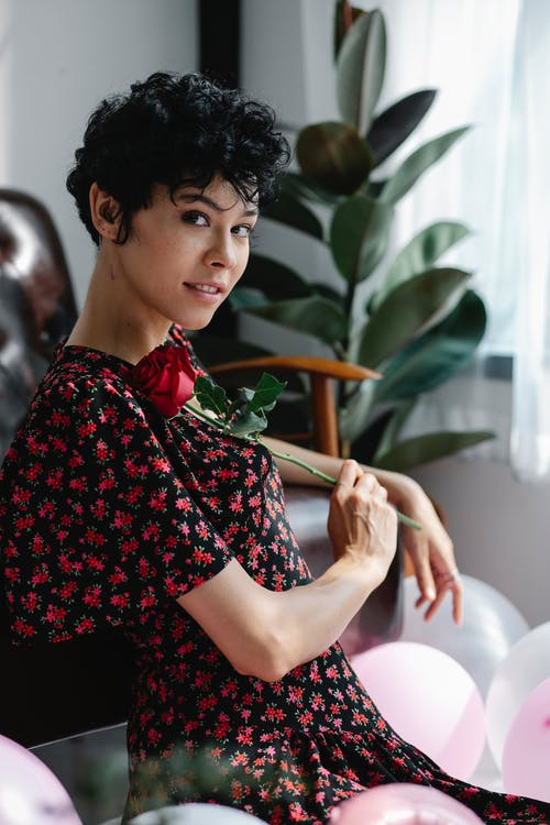 Side view of charming curly haired female with fresh rose among balloons against potted plant and looking at camera