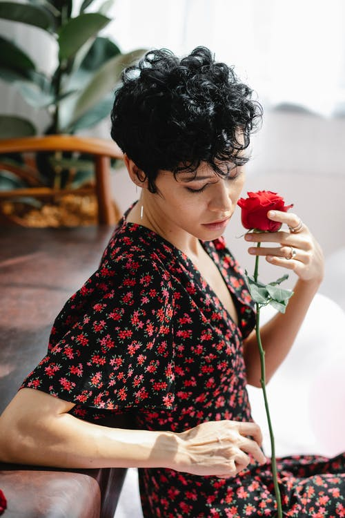 High angle side view of gentle female with curly hair sitting with blooming rose and looking down