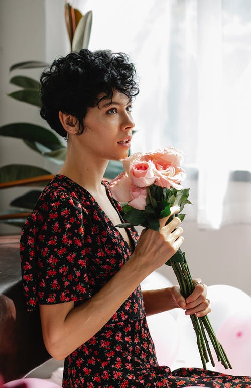 Side view of female wearing dress smelling bouquet of fresh roses sitting near balloons and looking away