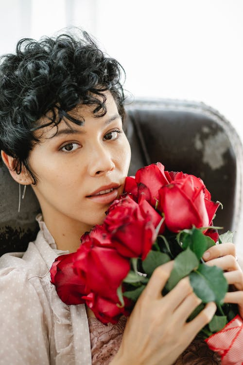 Charming female with short hair looking at camera while sitting in armchair with bouquet of blooming flowers in room during occasion