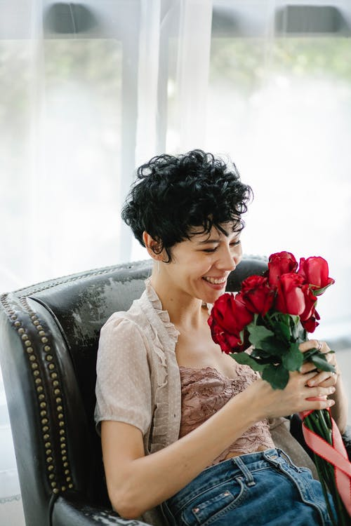 Positive female in casual wear looking at bouquet of red flowers while sitting on comfortable armchair near window in light room
