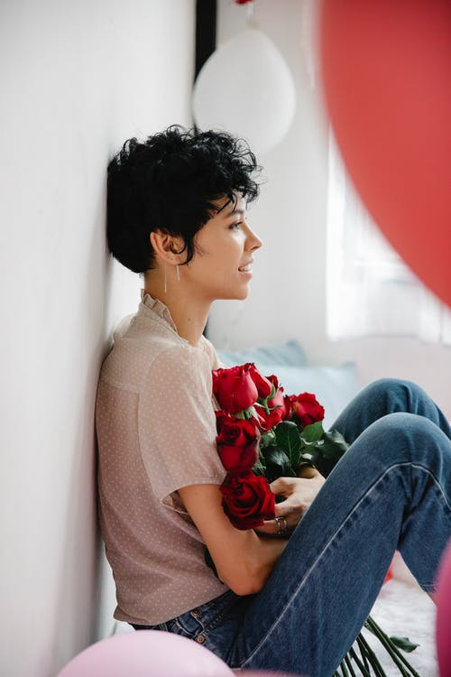 Happy young ethnic woman sitting on floor with roses bouquet in hands
