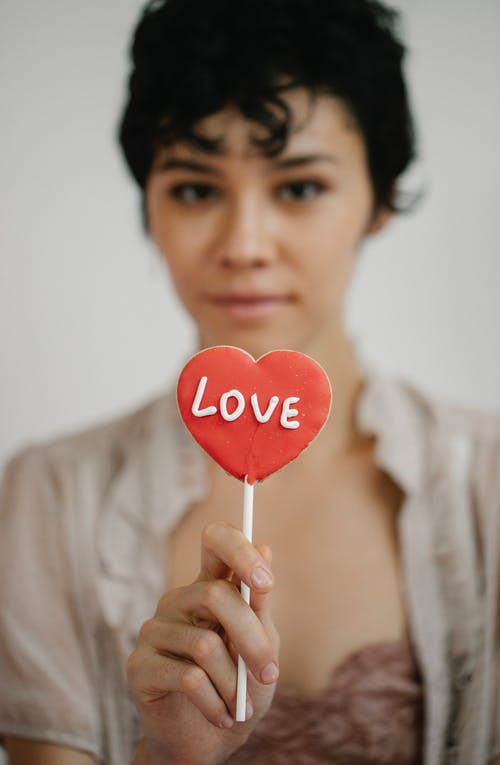 Trendy young ethnic woman showing heart shaped lollipop