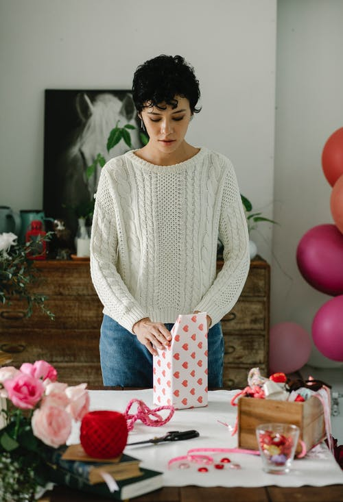 Concentrated young ethnic female with dark short hair in casual clothes standing at table and wrapping gift box in room decorated with balloons during Saint Valentine Day