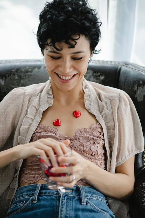 Cheerful young ethnic lady with dark short hair smiling and putting foiled heart chocolates on body while sitting in comfortable armchair