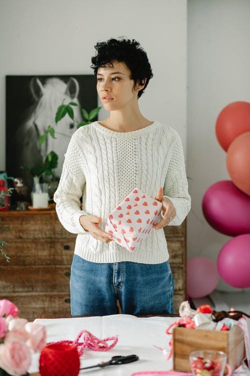 Stylish young ethnic female with curly short hair wrapping gift box with paper and ribbons and looking away in decorated apartment in daylight