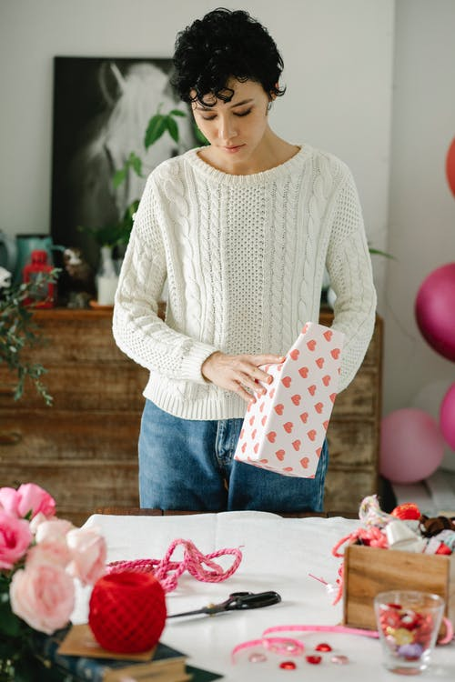 Young ethnic female millennial with short dark hair in stylish knitted sweater standing at table with various decoration items and wrapping gift box