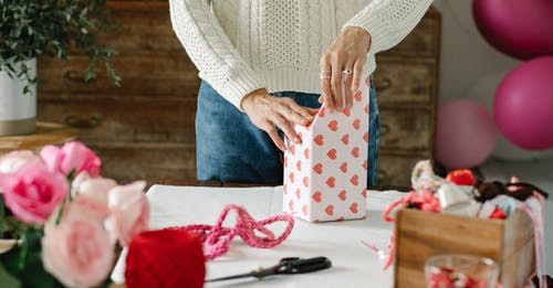 Crop anonymous lady decorating gift box with wrapping paper with red hearts while standing at table with ribbons and flowers
