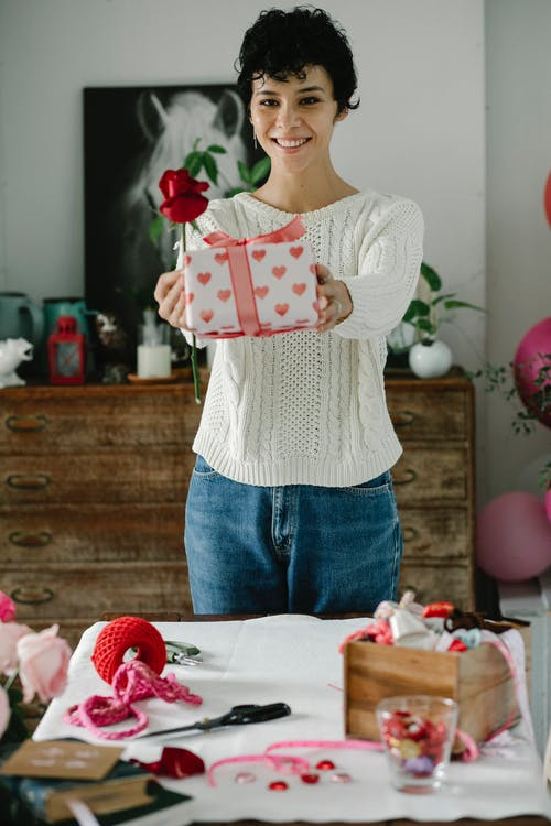 Cheerful young ethnic female with short curly hair in casual clothes smiling while demonstrating wrapped gift box and red rose and standing at table at home