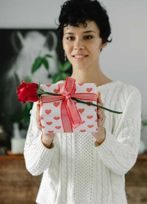 Content young ethnic female demonstrating gift box and red rose tied with ribbon