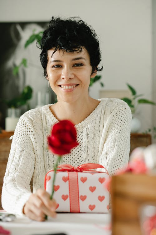 Young ethnic woman smiling at camera and sitting at table with present box and rose