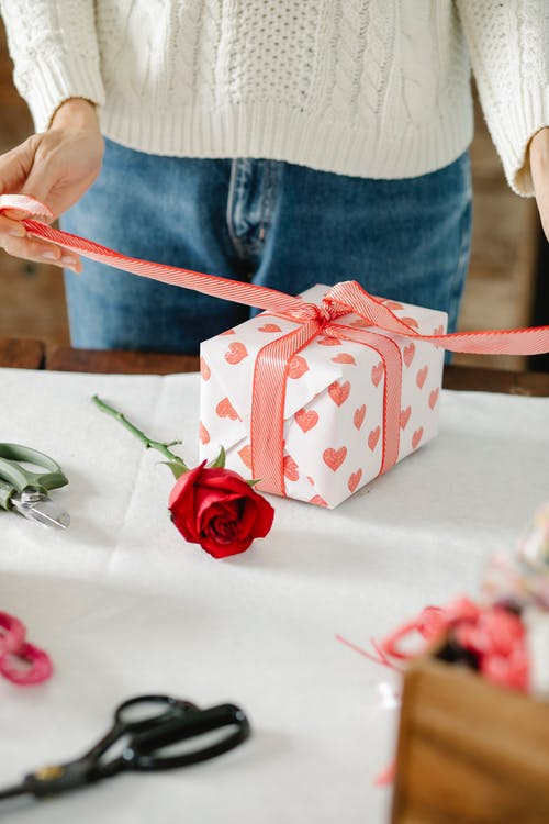 Unrecognizable woman tying bow on present box on Saint Valentine Day