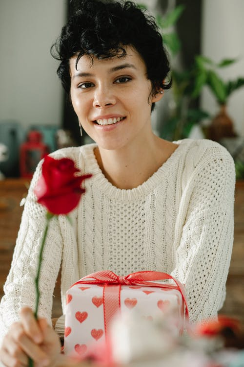 Smiling woman with rose at table with gift box