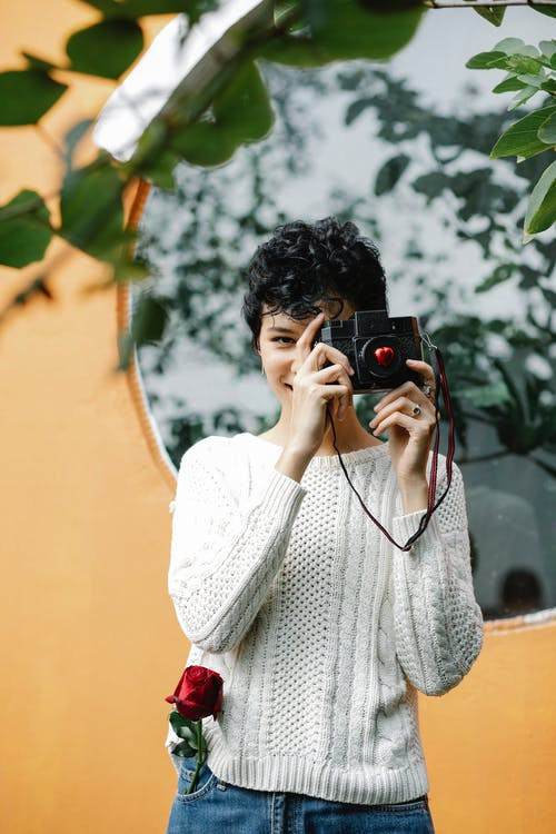 Cheerful woman taking photo with camera