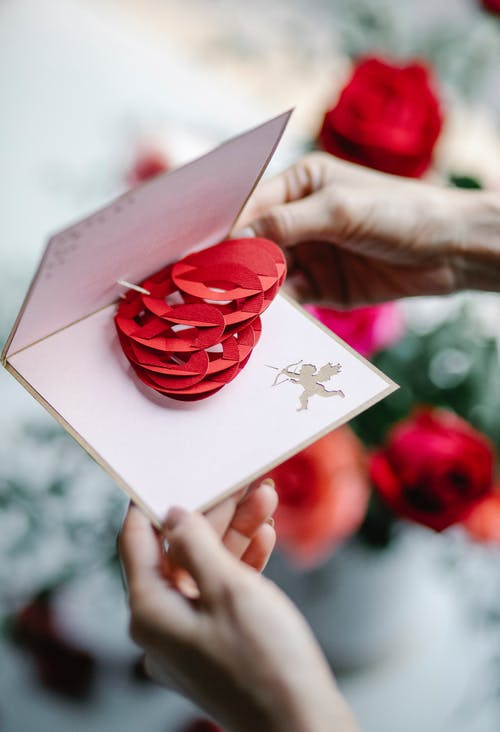 Faceless woman opening pop up gift card with decorative heart