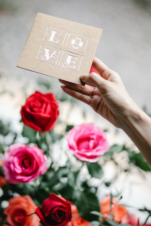 Crop anonymous female showing greeting card with Love title above blossoming rose bouquet during festive event