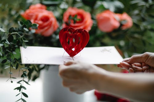 Crop woman showing pop up gift card with decorative heart