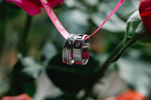 Closeup of rings with engraved Love inscription hanging on pink ribbon near colorful flowers with green stems on blurred background during romantic holiday