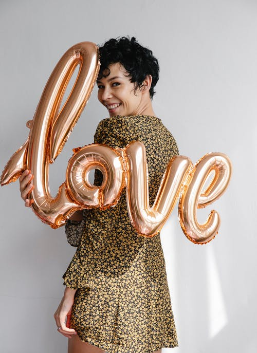 Positive female with golden foil balloons with romantic word smiling and looking at camera on white background during holiday celebration
