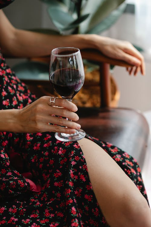 Crop woman with wineglass in room