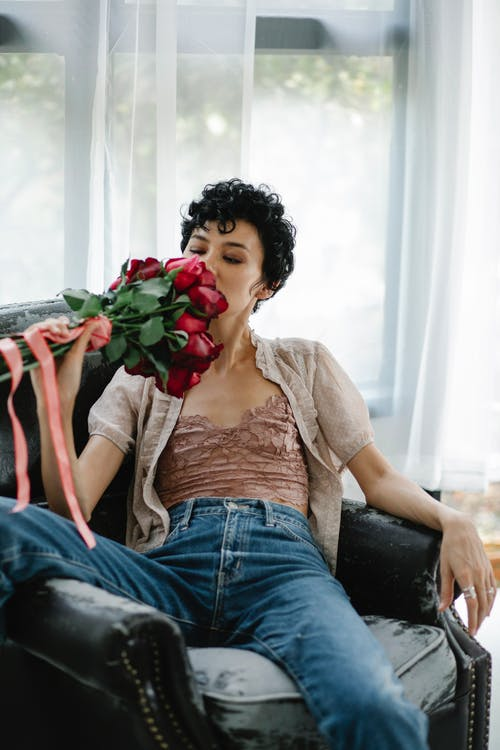 Relaxed female in casual clothes with bouquet of red flowers in hand sitting in comfortable armchair near window in room
