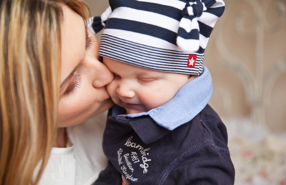 A mother kissing her baby. | Photo: Pexels