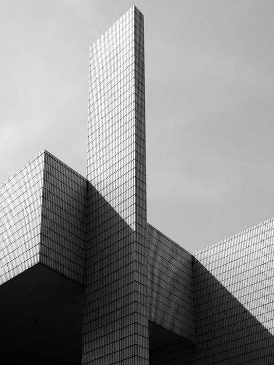 From below black and white of contemporary geometric construction exterior with tall walls under light cloudy sky in sunny day