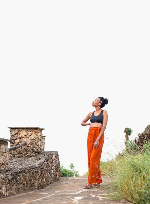 Woman in Orange Dress Standing on Brown Rock