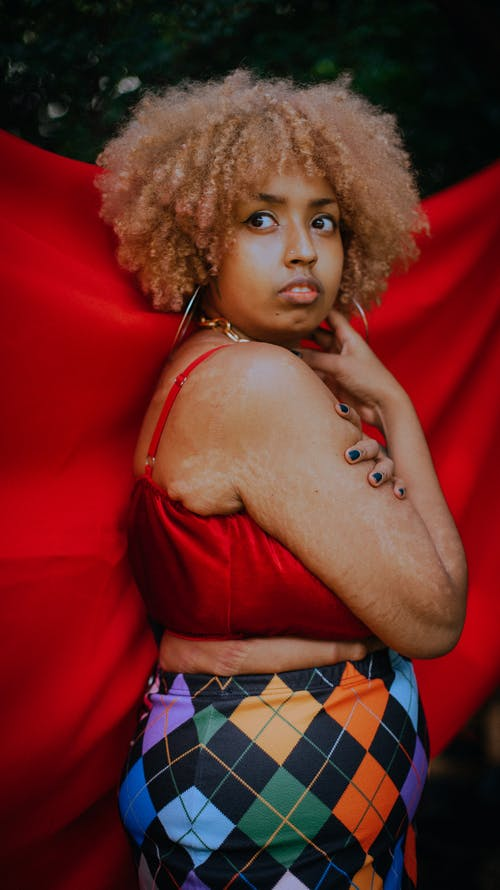Side view of plus size African American female with curly hair showing imperfect skin with stretch marks against red cloth and looking away