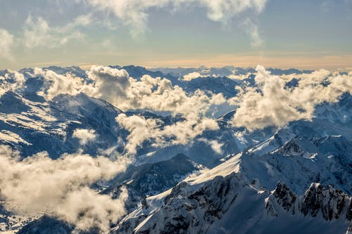 From above picturesque view of high mounts with snow under cloudy sky on sunny day in winter