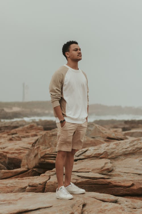 Full body of African American male in casual clothes standing on stony coast near waving river in cloudy day