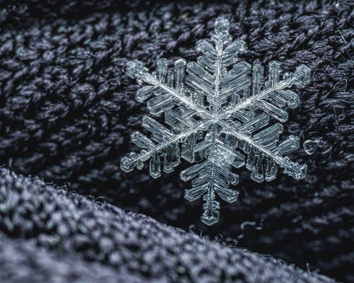 Macro shot of delicate glass snowflake placed on dark woolen surface of warm textile
