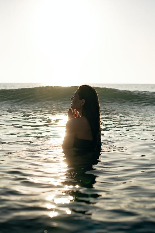 Side view of tranquil young female tourist with long dark hair standing in waving ocean with closed eyes and enjoying summer sunset